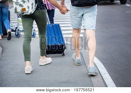 A  couple of travellers in a casual dress with backpacks crossing a road through zebra near airport or station.