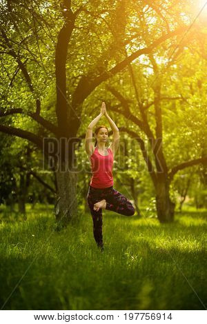 Woman practcing yoga, standing in tree pose with raised hands. Female in orning garden doing Vrksasana with raised hands.