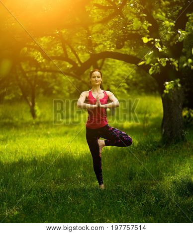 Young woman balancing in tree pose practicing yoga. Female outdoors doing Vrksasana. Toned image.
