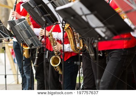 brass band, musical instrument, orchestra concept - festive performance of saxophones and clarinet, closeup on sheet music stands and sax, musicians in red concert jackets, selective focus