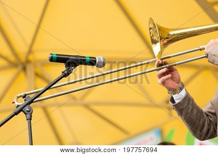 brass band, musical instrument and orchestra concept - closeup hands of male man playing trombone to external microphone on yellow background, performance of musician in concert suit, selective focus