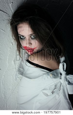 pretty fun crazy girl with fluffy hair and smeared cosmetics near wall looking at camera