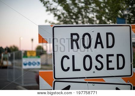 Sign stating that the road is closed as the sun sets in the background