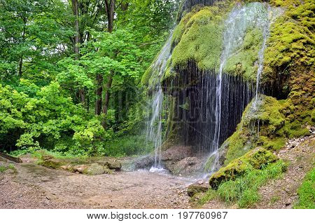 Waterfall With A Cave Among A Green Garden