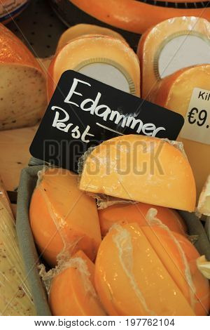 Traditional Dutch cheeses on display in a store (text on labels: price and product information in Dutch the famous Edammer cheese)