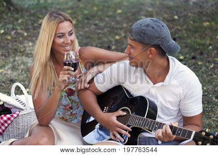 Smiling Man Singing Serenade To His Lady Playing Guitar