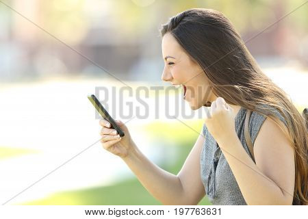 Profile Of An Excited Woman Using A Phone