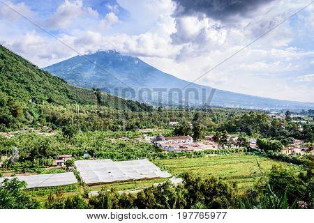 San Cristobal el Cerrito, Guatemala - July 10 2017: View from San Cristobal el Cerrito of Agua volcano & San Cristobal el Bajo outside the UNESCO World Heritage Site of Antigua