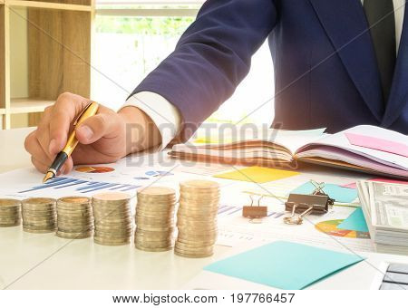 Businessman has a pen in his right hand analysis of graph data,On the desk there are coins dollars notebooks and flip charts placed.