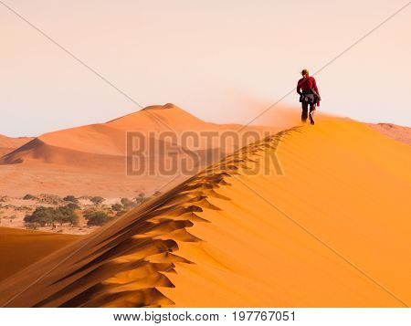 Woman walking on the ridge of red dune in windy weather, Sossusvlei, Namib desert, Namibia.