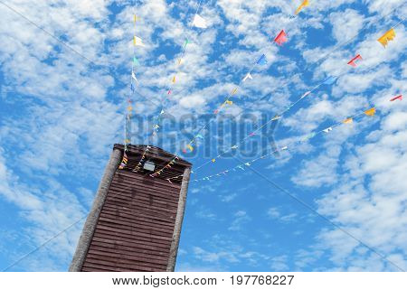 Old vintage wooden tower with blue sky background