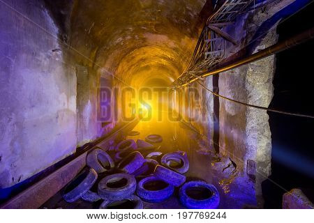 Abandoned flooded tunnel of cable collector, old rotten tires