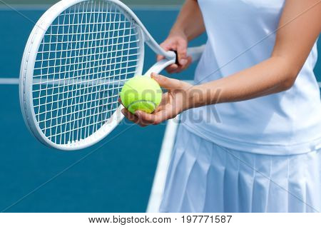 Tennis Player Holding Tennis Racket And Ball In Hand  On The Tennis Court.
