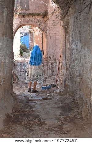 Woman sweeping entryway with broom in Peru