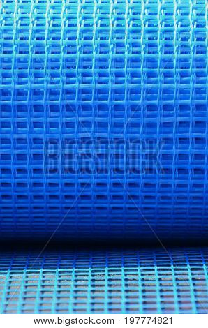 Close-up Texture Of A Blue Reinforcing Mesh Rolled Up In A Roll. Building Resource For Reinforcing W