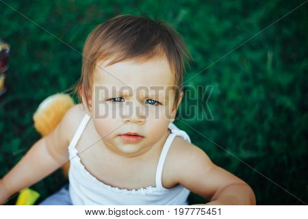 baby is seriously looking into the camera. She frowns. Sitting on grass. outdoor