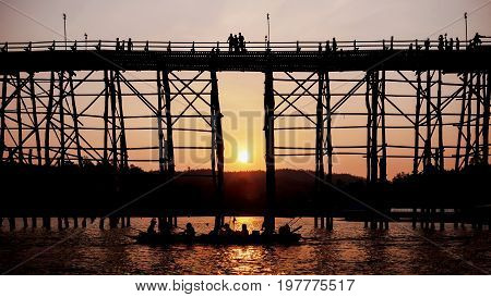 Silhouetted bridge at sunset in Sangkla Thailand .