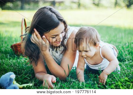 Mother and daughter lying on the grass. legged child