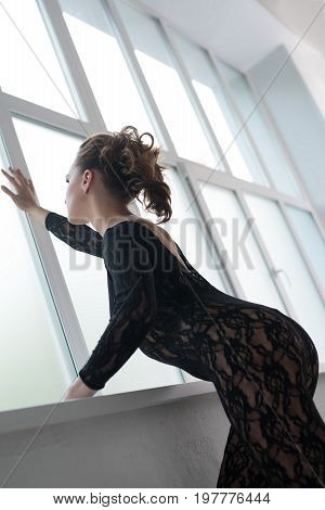 Slim girl with a curly tail hair style wearing black lace lingerie looking out the window