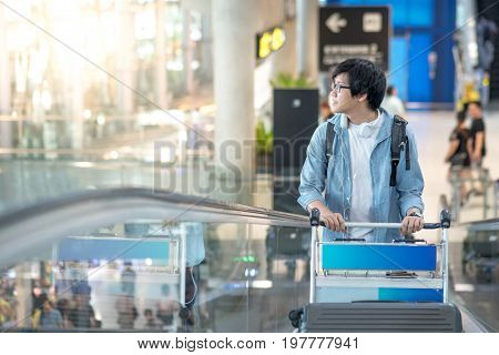 Young Asian man with airport trolley on escalator walking to check-in counter in the international airport terminal. travel abroad on vacation