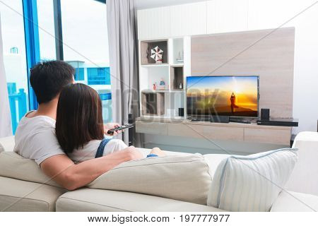 Happy family watches television while sitting on the sofa.