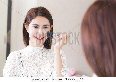 Asian woman putting makeup in home using a contour brush to apply blonze powder under cheek bones make-up mirror.