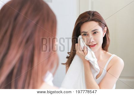 Young woman wiping her face with towel in bathroom.