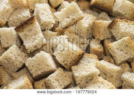 Crispy croutons of white bread lie on the heap.