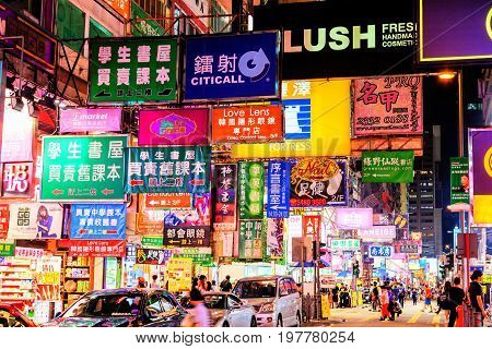 HONG KONG JULY 10 2017: Colorful billboard neon signs hang precariously on buildings along Nathan Road in Mongkok one of the busiest and most popular commercial areas in Hong Kong and a favorite place for visitors and locals to hang out and explore.