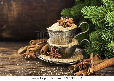 Melchior vintage cups with cane sugar, anise stars, Indian Indian cinnamon sticks on an aged wooden background surrounded by spruce spruce branches. Toned, with imitation of falling snow. Selective focus. Christmas decorations