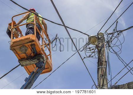 Utility Pole Worker Installs New Cables On An Electric Pole