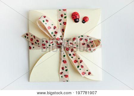 Gift envelope with bow and ladybugs on white background