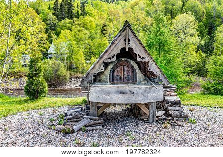 Petit-Saguenay Canada - June 2 2017: Wood log burning french fireplace by river in Quebec village