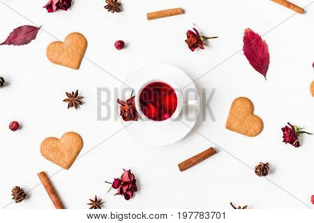 cup of fruit tea with autumn leaves cookie cinnamon sticks star anise cones dry roses autumn concept top view flat lay