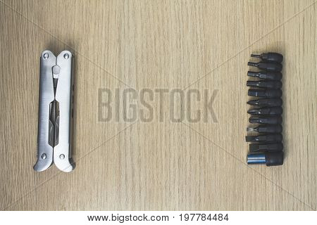 Metall multi tool for home works on wooden background