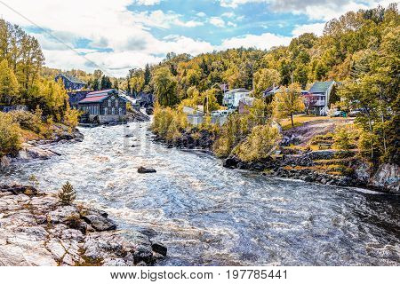 Chicoutimi Canada - June 3 2017: La Pulperie de Chicoutimi Regional Museum Pulp mill in Saguenay Quebec with river and water flowing in autumn
