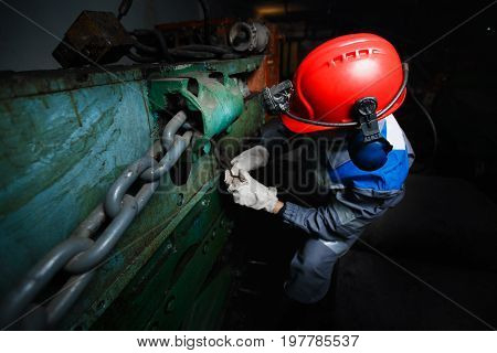 male miner in a underground mine is repairing a harvester, a sinker. Concept work in difficult conditions.
