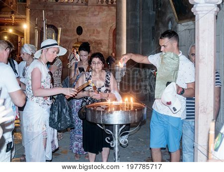 Jerusalem Israel July 14 2017 : Believers light candles in the Church of the Holy Sepulchre in the old city of Jerusalem Israel.