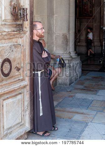 Jerusalem Israel July 14 2017 : The priest stands leaning on the door at the entrance to the Church of the Holy Sepulchre in the old city of Jerusalem Israel.