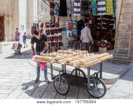 Jerusalem Israel July 14 2017 : Street vendor sells sweets near the entrance to the Suq Aftimos market in Muristan Street in the old city of Jerusalem Israel.