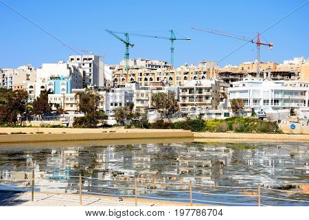 BUGIBBA, MALTA - MARCH 31, 2017 - View of salt pans with buildings and construction cranes to the rear in Salina Bay Bugibba Malta Europe, March 31, 2017.