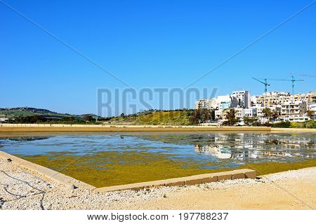 View of salt pans with buildings and construction cranes to the rear in Salina Bay Bugibba Malta Europe.