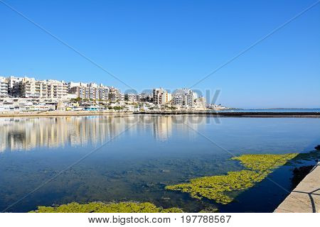 BUGIBBA, MALTA - MARCH 31, 2017 - View of salt pans with buildings to the rear in Salina Bay Bugibba Malta Europe, March 31, 2017.