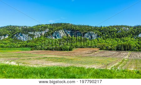 Quebec Farm Landscape With Brown Plowed Field In Summer With Mountain Cliffs In Canada
