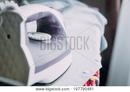 Ironing Clothes Shirt With Iron On Ironing Board