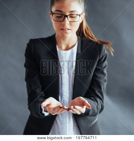 smiling young woman showing something on the palm of both hands open.