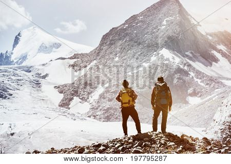 Trekking concept with two friends on mountains background. Spacefor text