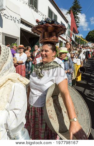 ESTREITO DE CAMARA DE LOBOS PORTUGAL - SEPTEMBER 10 2016: Woman wearing in traditional costume with a basket of grapes on her head at Madeira Wine Festival in Estreito de Camara de Lobos Madeira Portugal