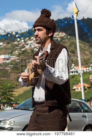 ESTREITO DE CAMARA DE LOBOS PORTUGAL - SEPTEMBER 10 2016: Folk music group in local costumes performs a folk dance at Madeira Wine Festival in Esterito de Camara de Lobos on the Madeira Portugal. The Madeira Wine Festival honors the grape harvest with a c
