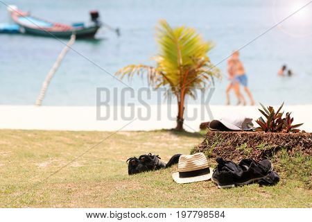 Belongings on the lawn with tourist activities on the beach background